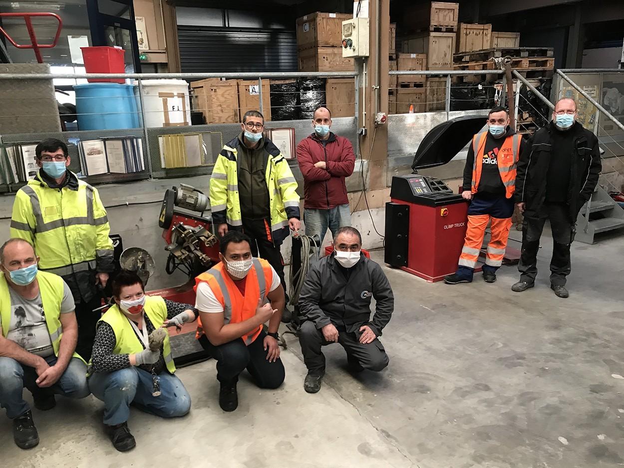 Plusieurs personnes en tenues de sécurité pose pour une photo au sein d'un atelier.